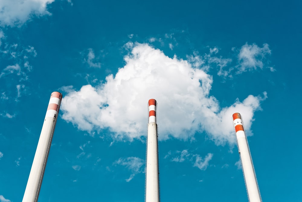three white poles under white clouds and blue sky during daytime