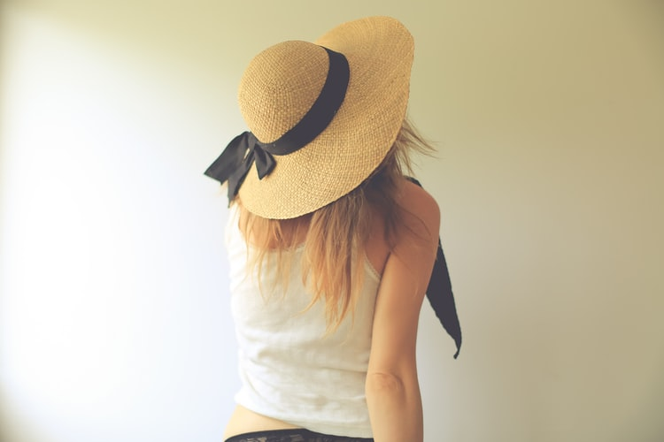 a girl looking away wearing a straw wide brim hat with a black ribbon on it