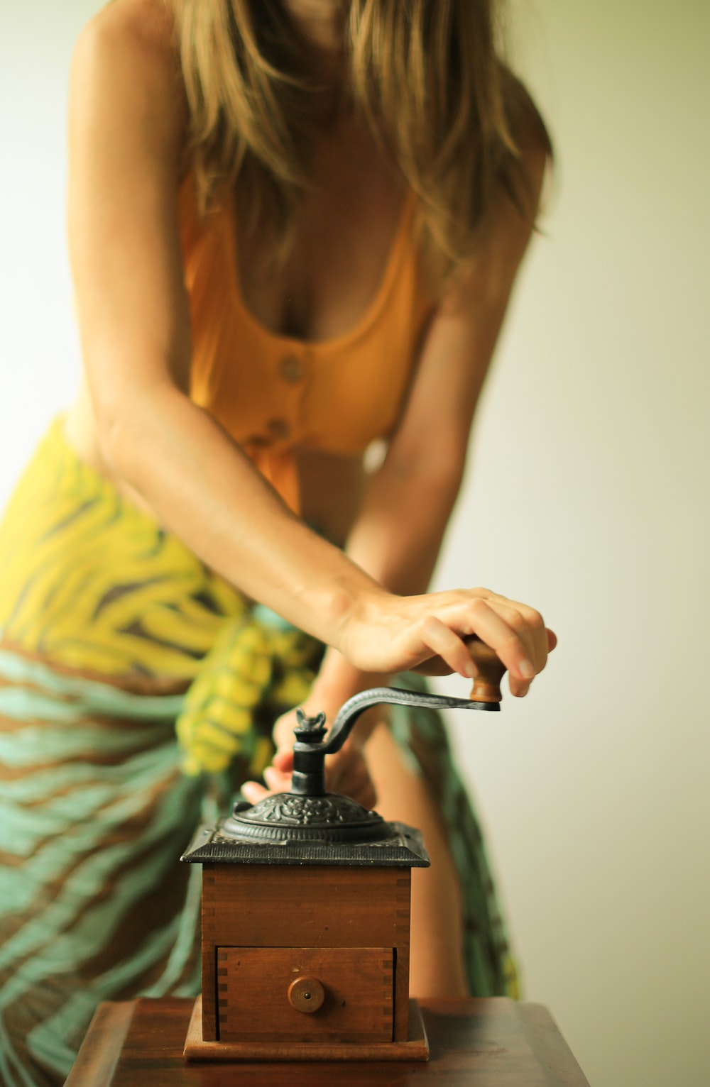 woman holding manual coffee grinder