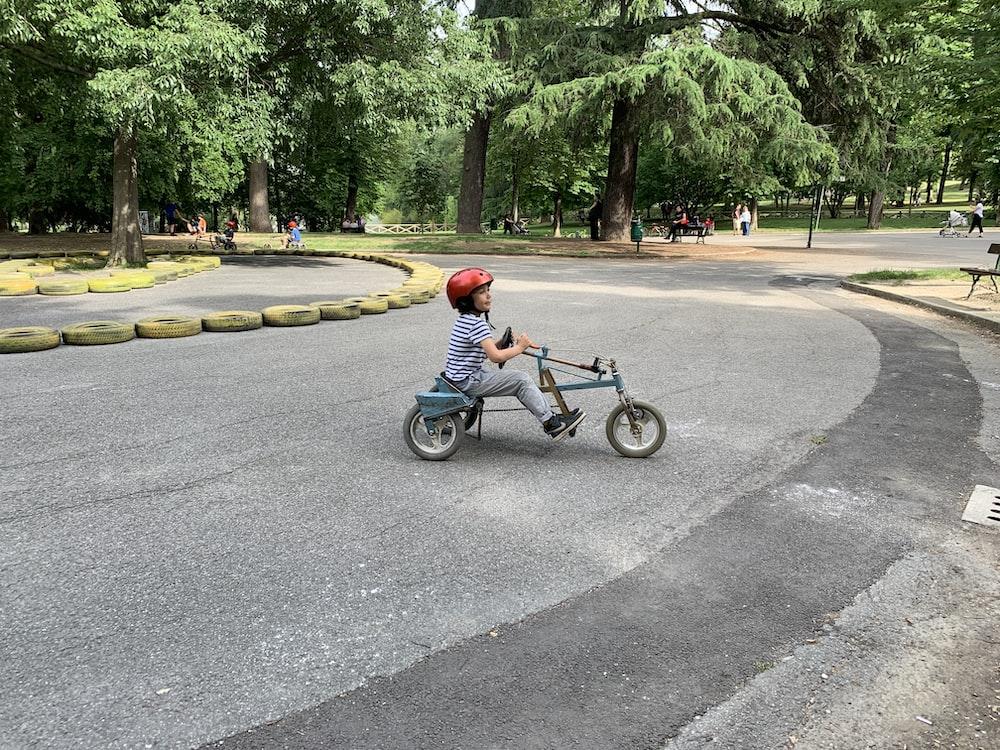 child riding on trike on park