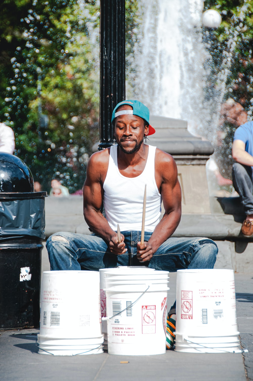 man in white tank top playing with three white plastic buckets