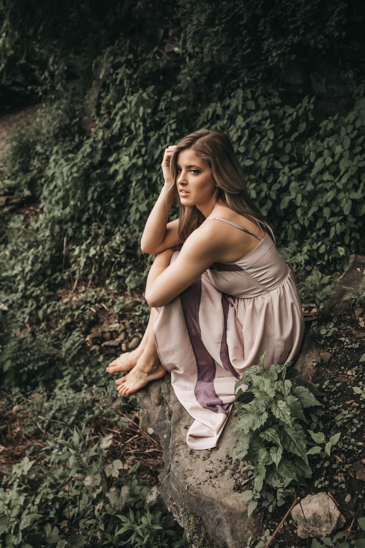 woman in gray spaghetti strap dress sitting on rock cliff