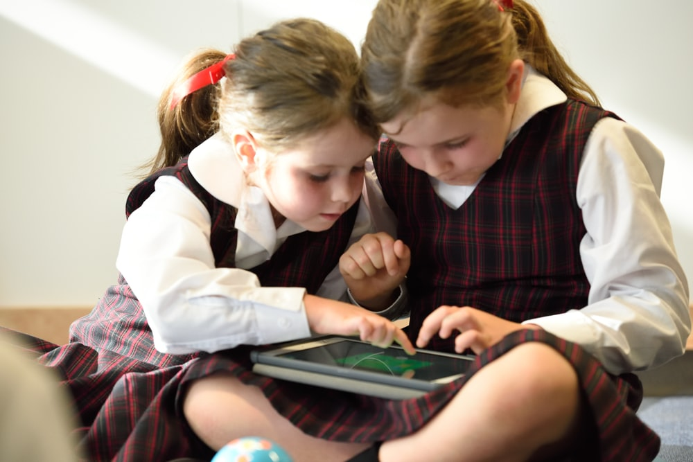 two girls playing tablet computer