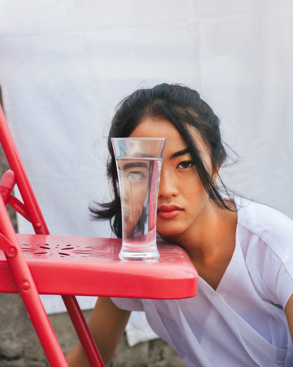 woman in white top looking through glass of water