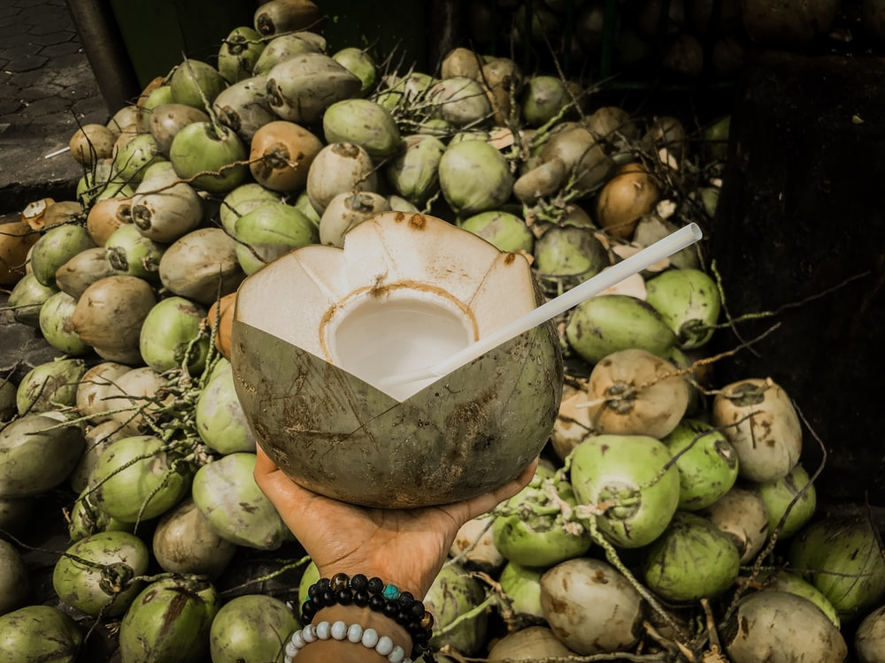 green coconut on human hand