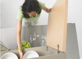 woman in green polo shirt and white pants standing in front of open cupboard