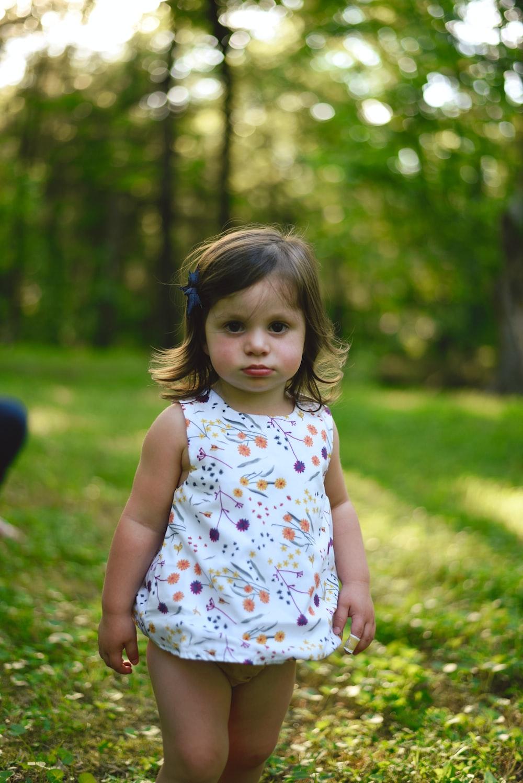 toddler girl standing on grass
