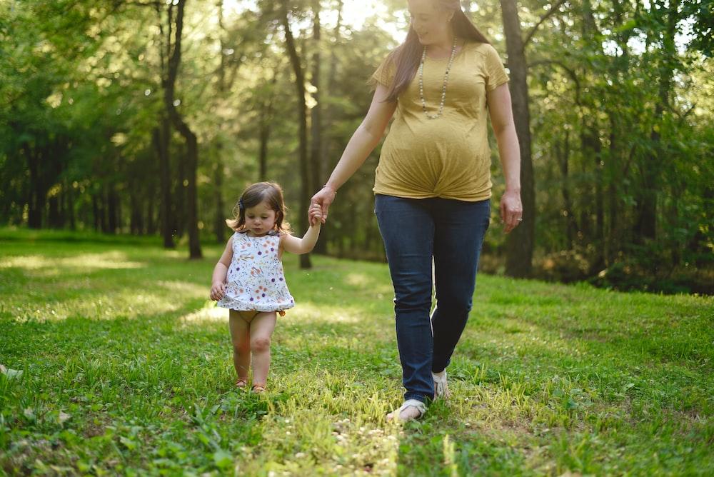 pregnant woman walking beside girl