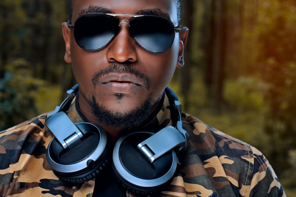 man wearing sunglasses and grey and black headphones
