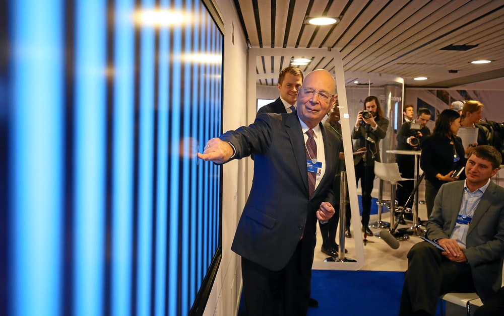 man in black suit pointing in blue screen on wall