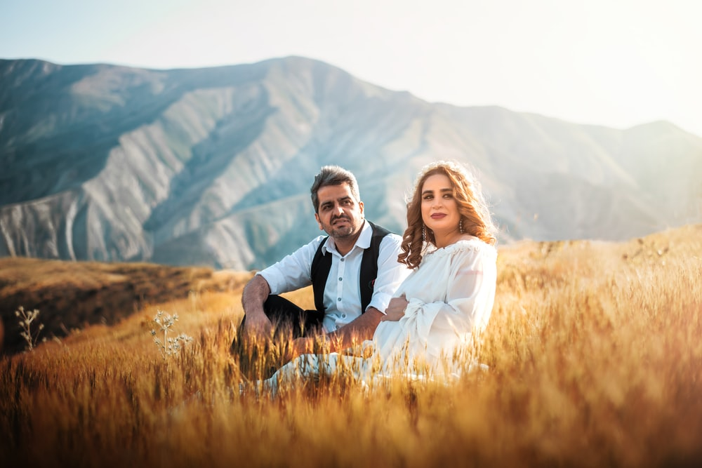 man and woman sitting next to each other with mountain view