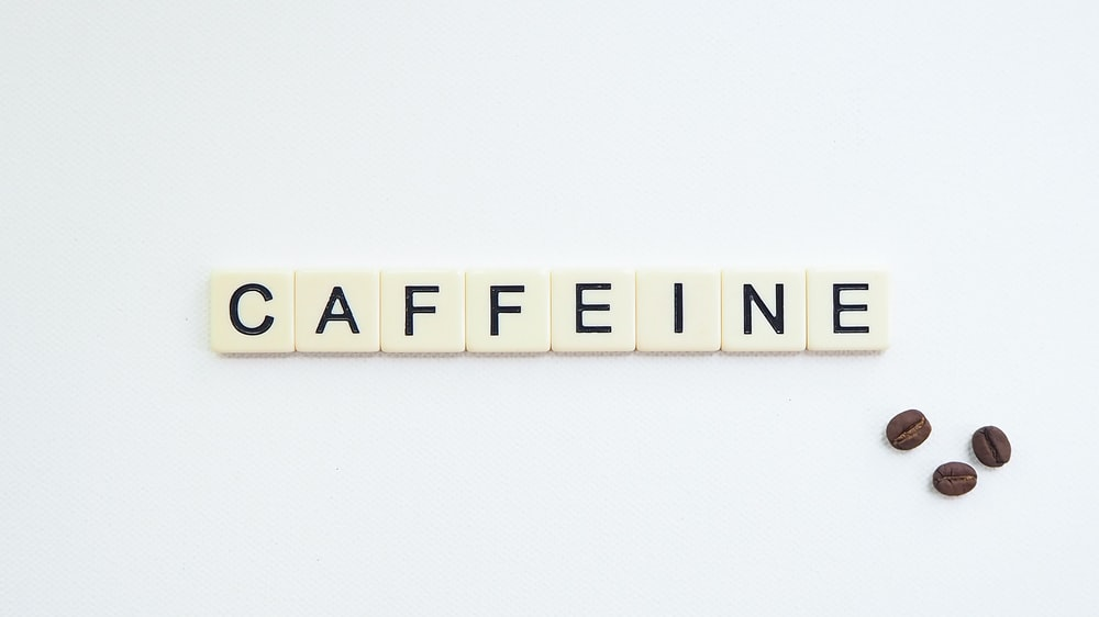 white and black scrabble tiles spelling caffeine