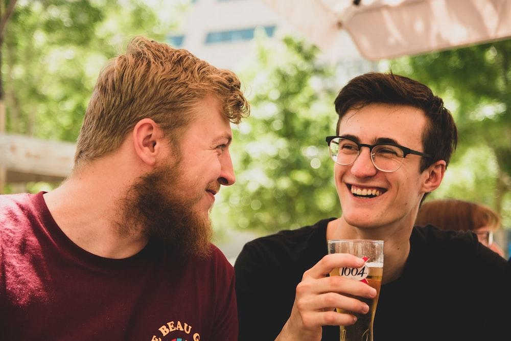 two men smiling near trees