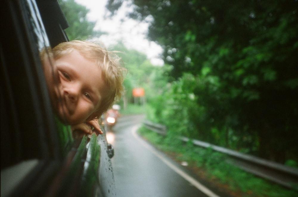 child peeking from vehicle window