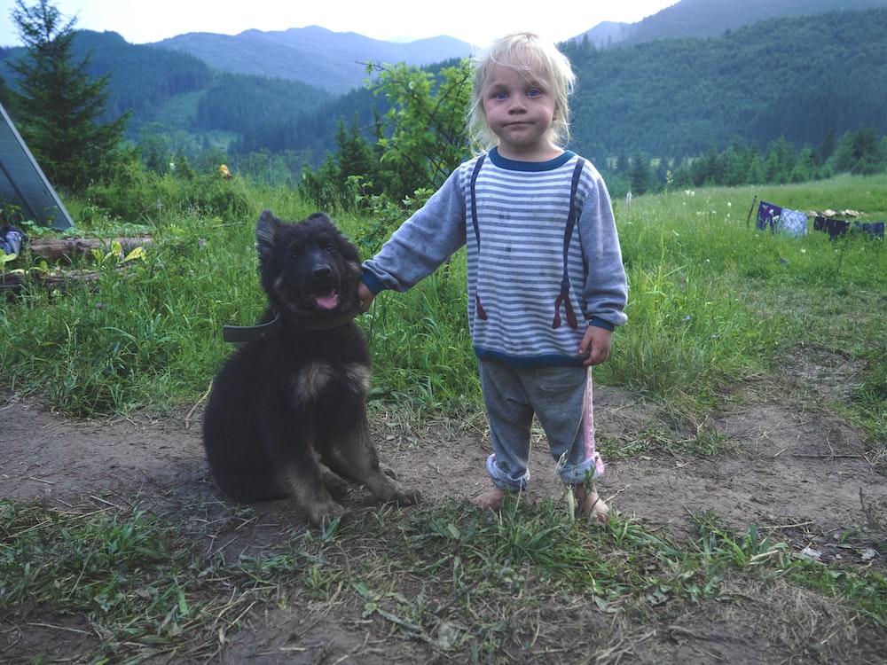 girl wearing blue striped shirt beside black dog