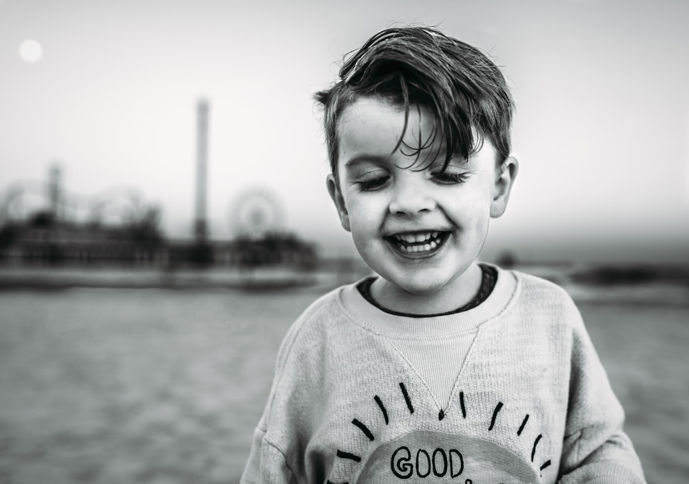 grayscale photo of smiling boy in sweater