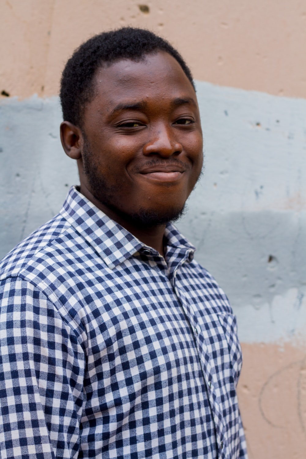 smiling man in front of wall