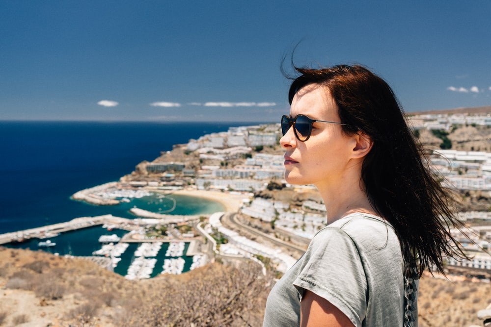 woman in grey t-shirt standing on top of hill overlooking city and sea