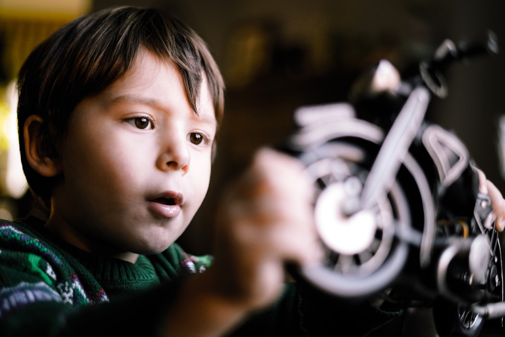 boy wearing green sweater playing with motorcycle toy