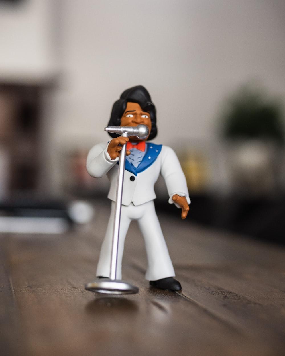 man singing figurine on selective focus photography