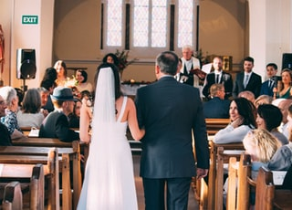 bride walking together with man inside church surrounded with people