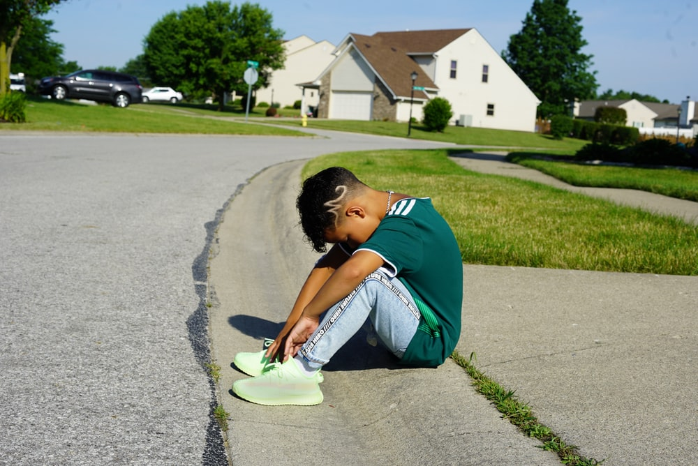 boy sits on pavement and head down
