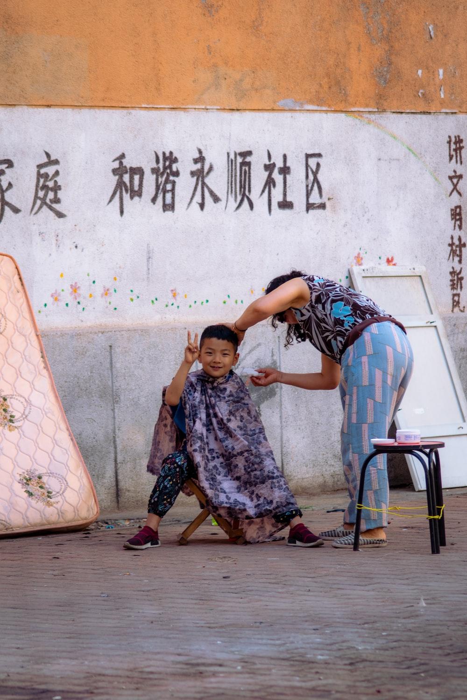 boy sitting on stool beside standing woman near wall