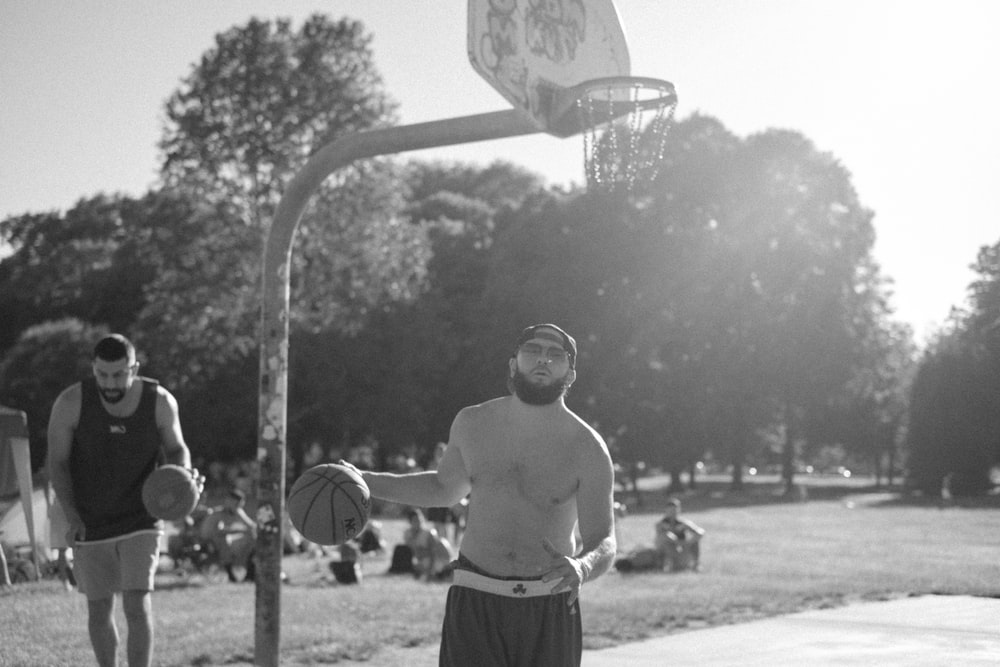 grayscale photography of two men playing basketball