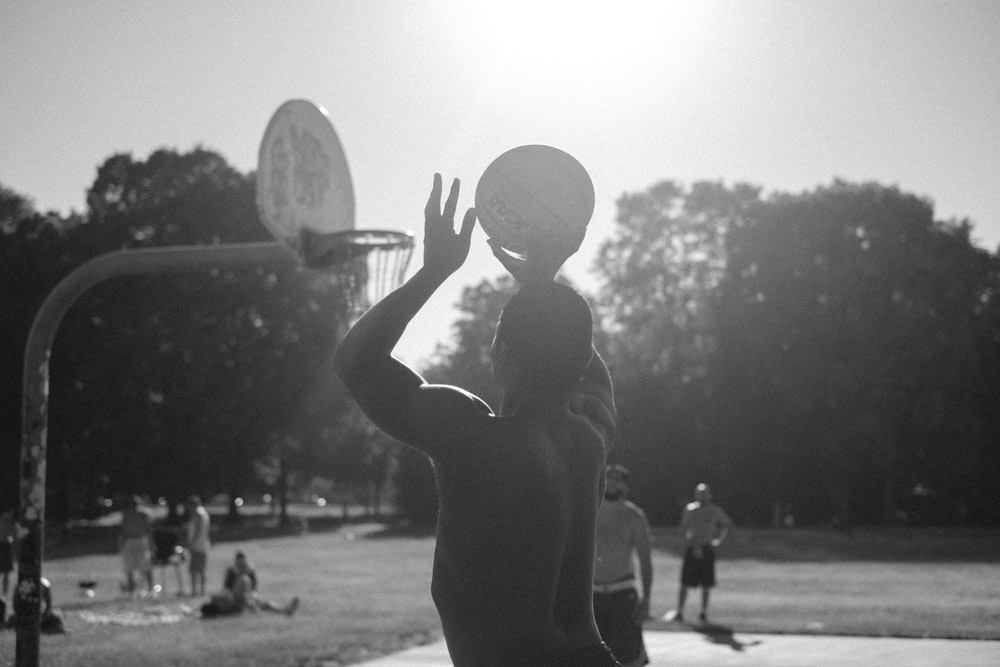grayscale photo of man playing basketball