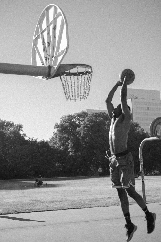 grayscale photography of man playing basketball