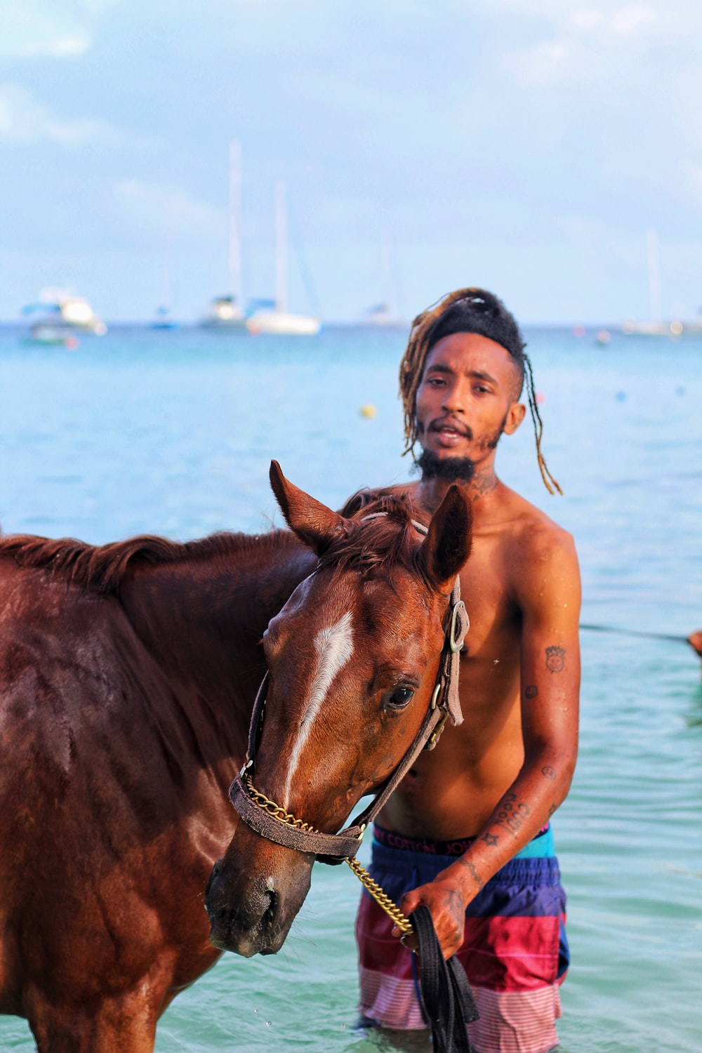 man standing on seashore with brown horse