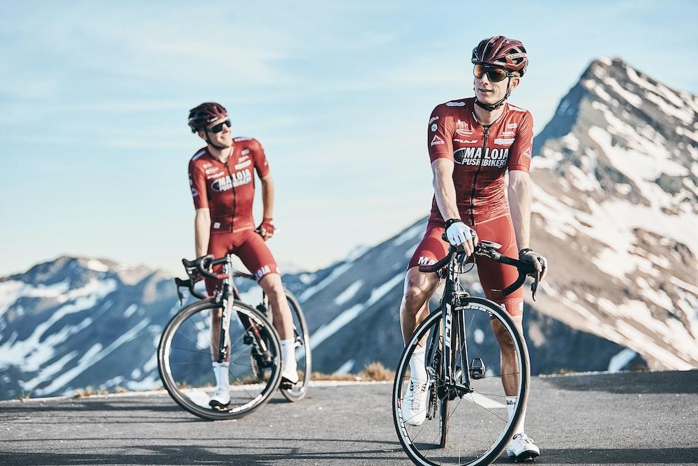 two men biking on road viewing mountain