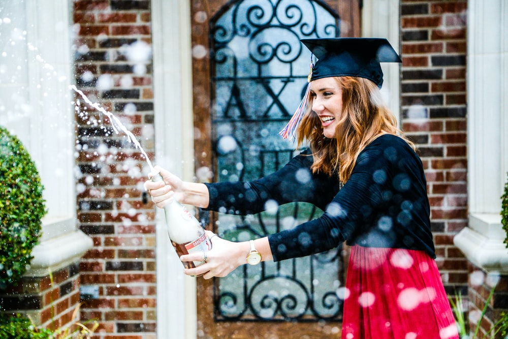 woman in black long-sleeved blazer wearing graduation cap holding wine bottle