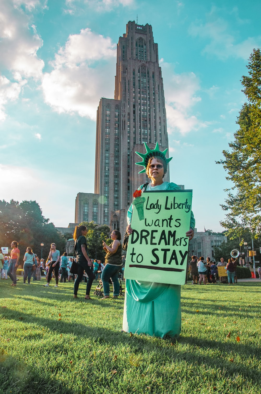 man holding Lady Liberty wants dreamers to stay signage