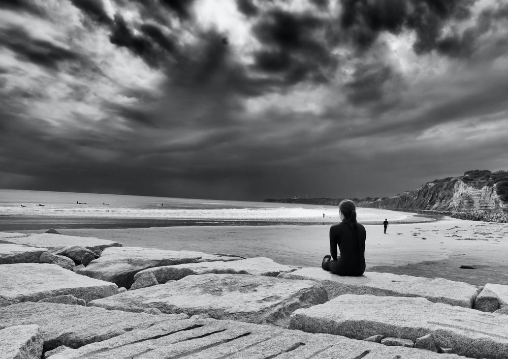 grayscale photo of person sitting in near ocean during daytime