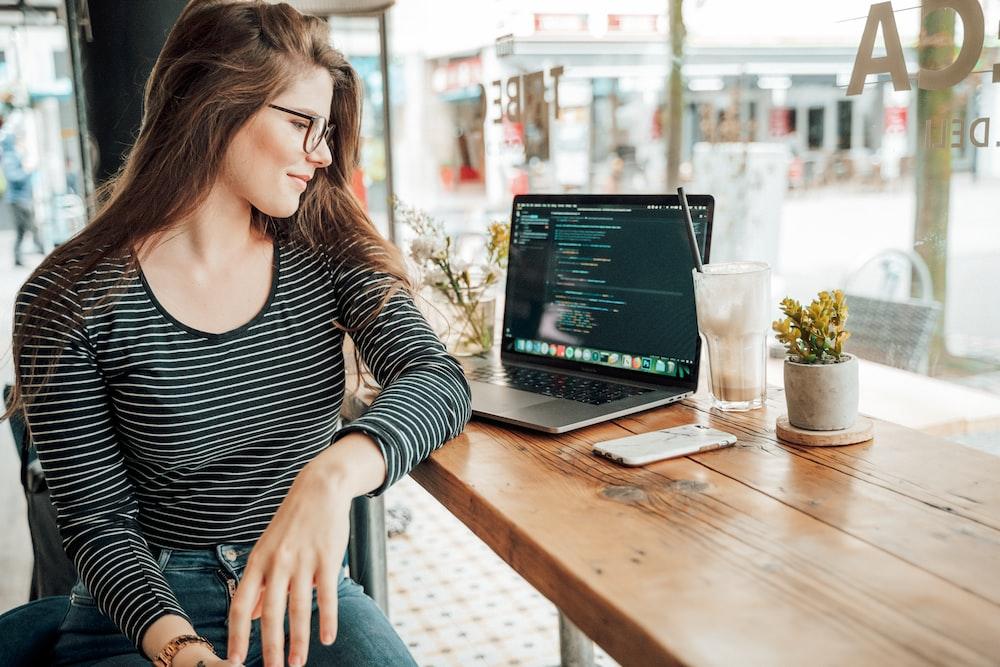 woman sits near laptop computer