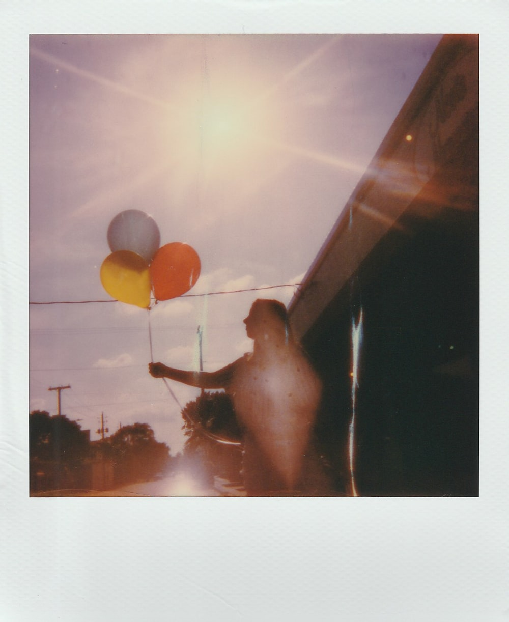 photo of a women holding three balloon close-up photography