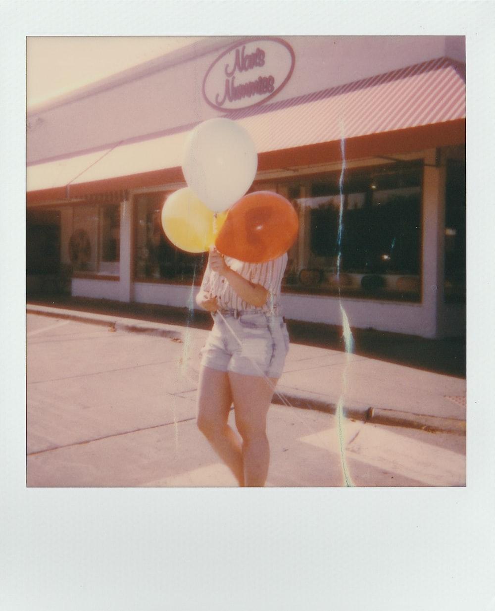 woman holding three balloons