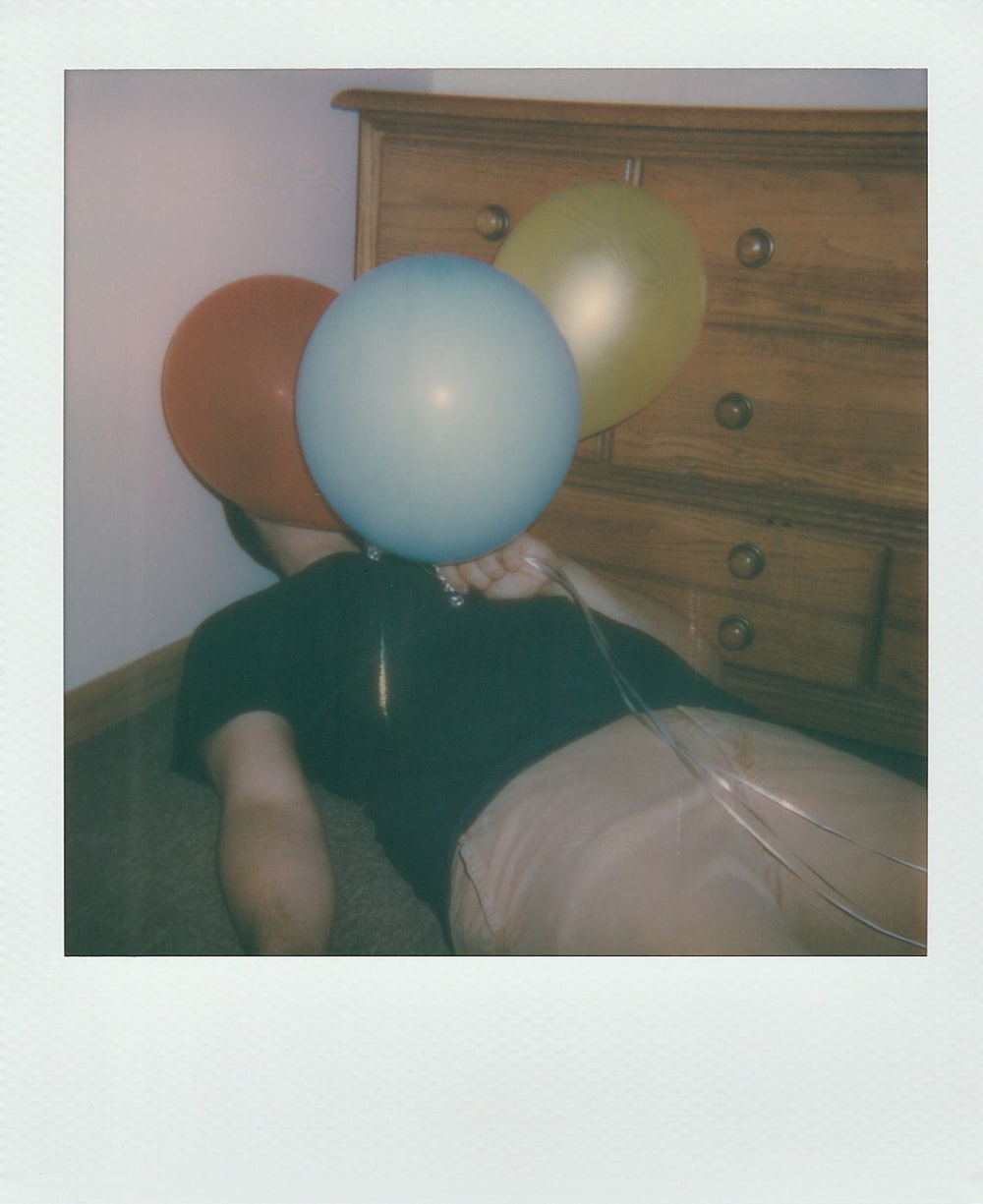 man holding three assorted-color balloons