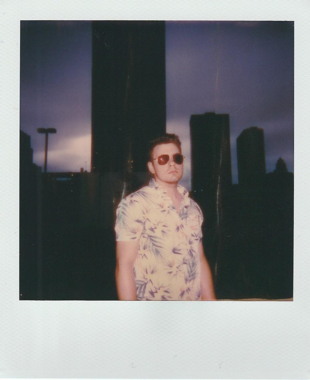 man wearing aviator sunglasses across city building