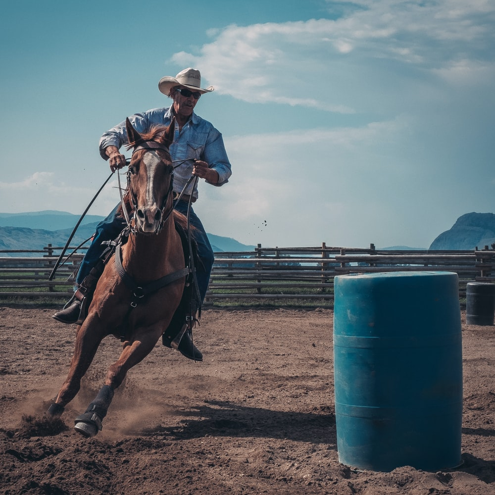 man in white cowboy hat riding a horse