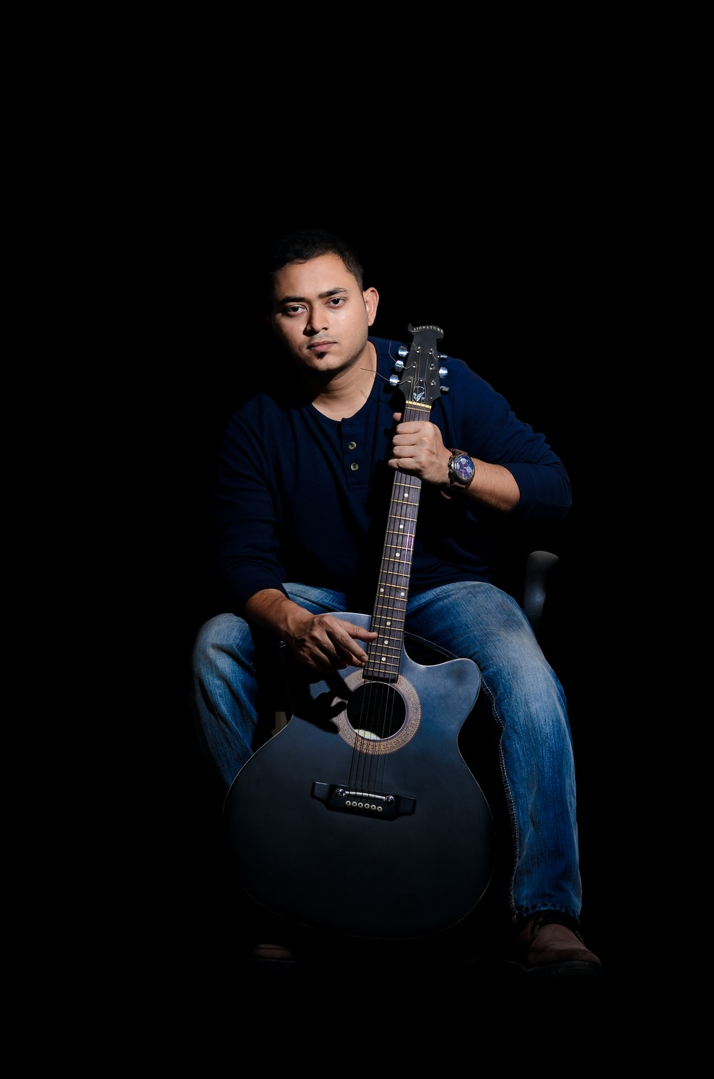 man sits while holding acoustic guitar on black background