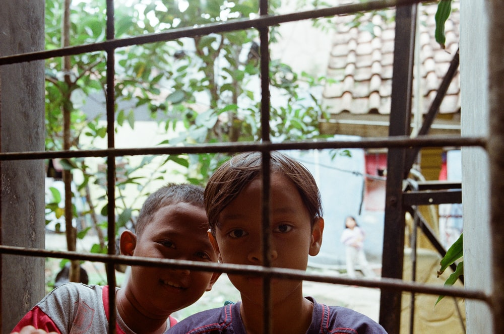 two toddlers behind window