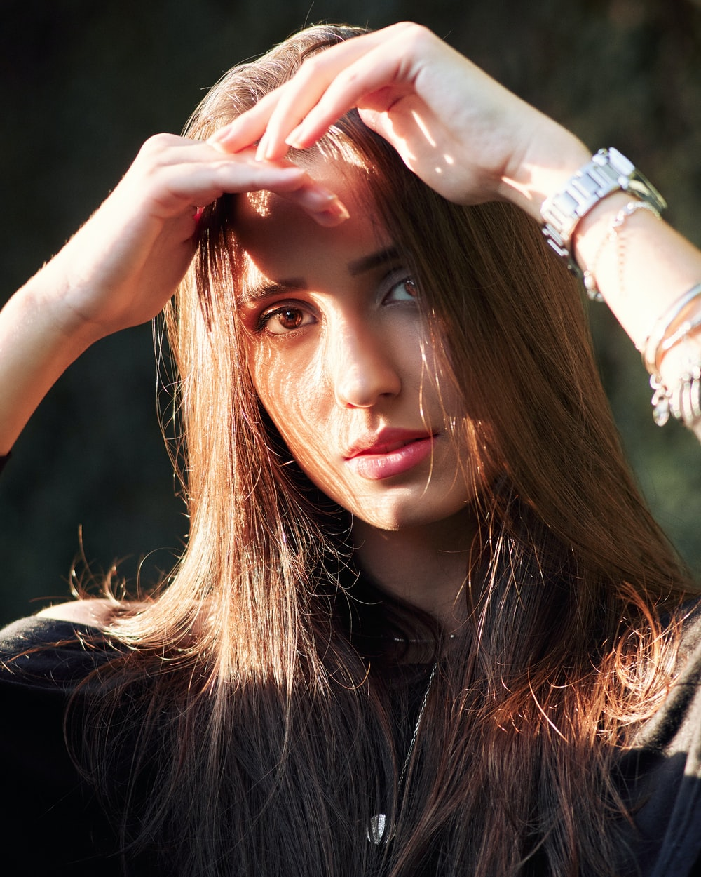 woman wearing black top both hands on forehead covering face from sunlight