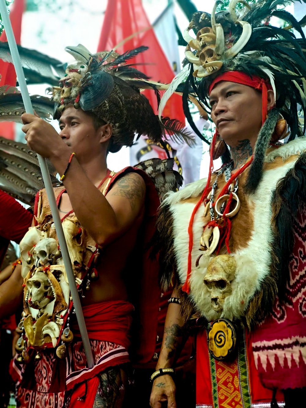 two men standing wearing Native American costume during daytime