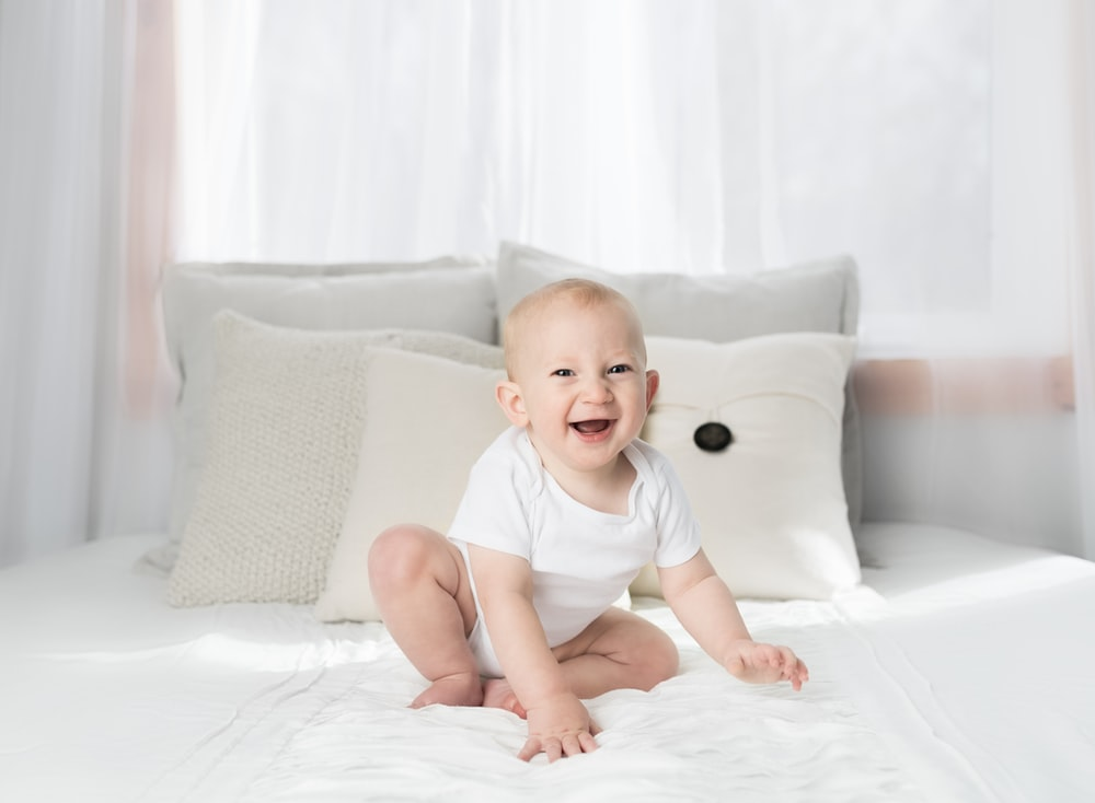 smiling baby sitting on white bed