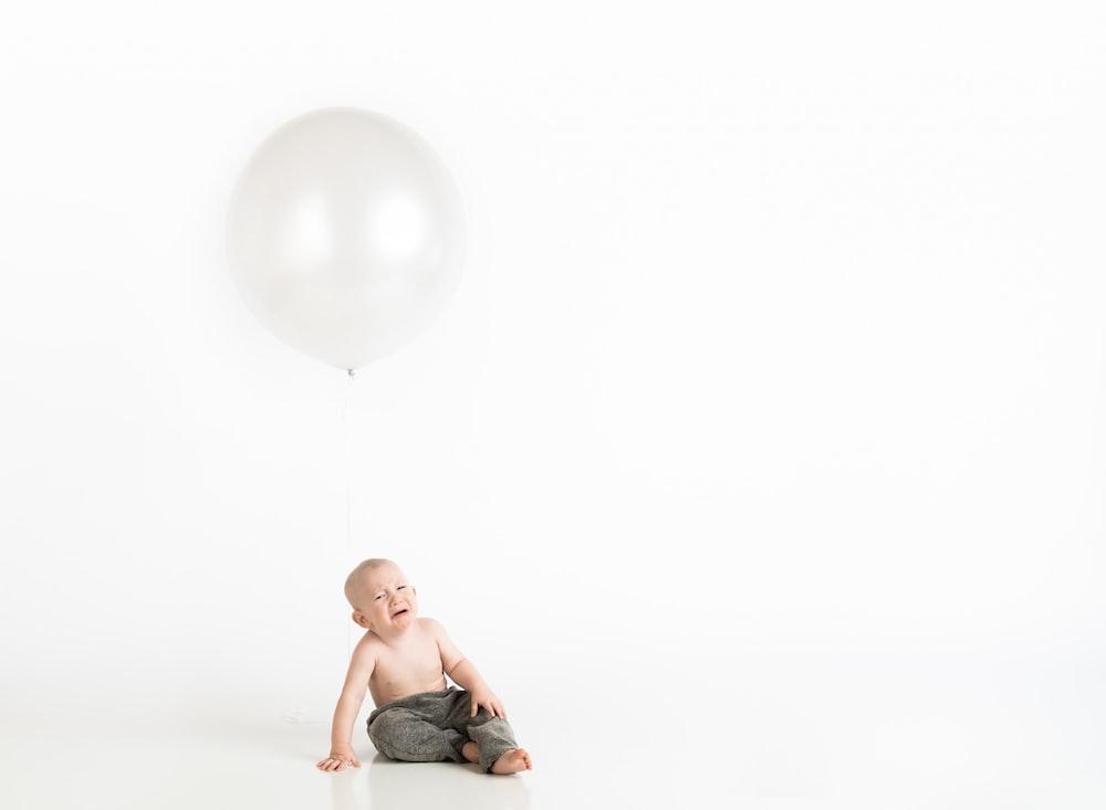 kid wearing gray pants close-up photography