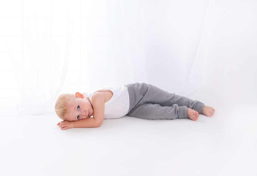 boy wearing white tank top lying on white surface close-up photography