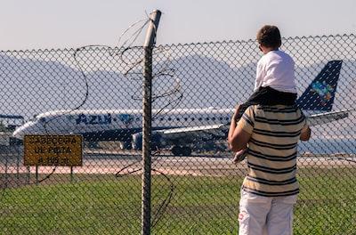 man carrying boy facing white passenger plane rio de janeiro teams background