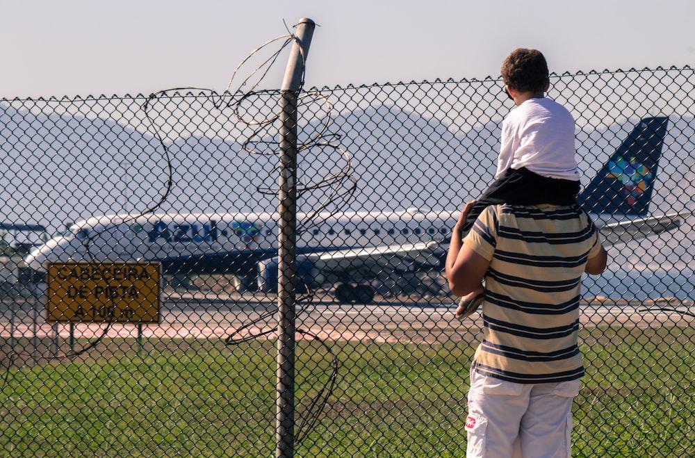 man carrying boy facing white passenger plane